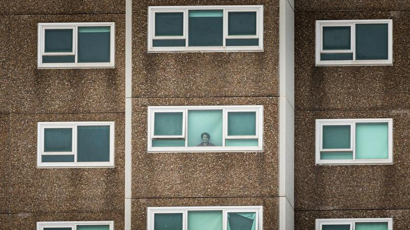 A woman in one of the locked-down public housing towers in Melbourne's west stares out the window