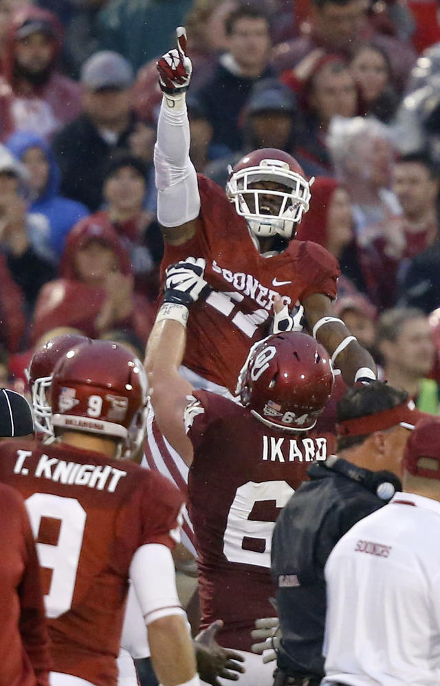 Oklahoma wide receiver Lacoltan Bester (11) celebrates a touchdown against Texas Tech with teammate Gabe Ikard (64) in the third quarter of an NCAA college football game in Norman, Okla., Saturday, Oct. 26, 2013. Oklahoma won 38-30. (AP Photo/Sue Ogrocki)