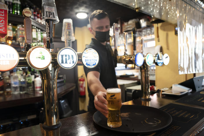 A member of staff serves a drink, as pubs, cafes and restaurants in England reopen indoors under the latest easing of the coronavirus lockdown, in Manchester, England, Monday, May 17, 2021. Pubs and restaurants across much of the U.K. are opening for indoor service for the first time since early January even as the prime minister urged people to be cautious amid the spread of a more contagious COVID-19 variant. (AP Photo Jon Super)