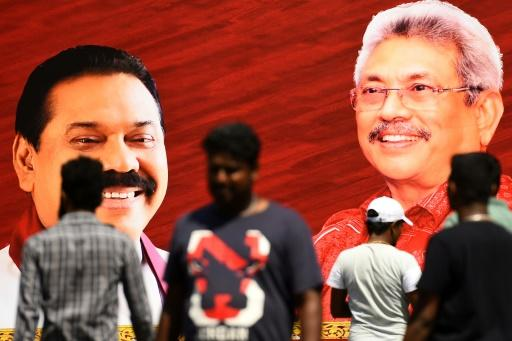 Pedestrians walk past a giant poster of Rajapaksa brothers Mahinda (left) and Gotabaya in Colombo