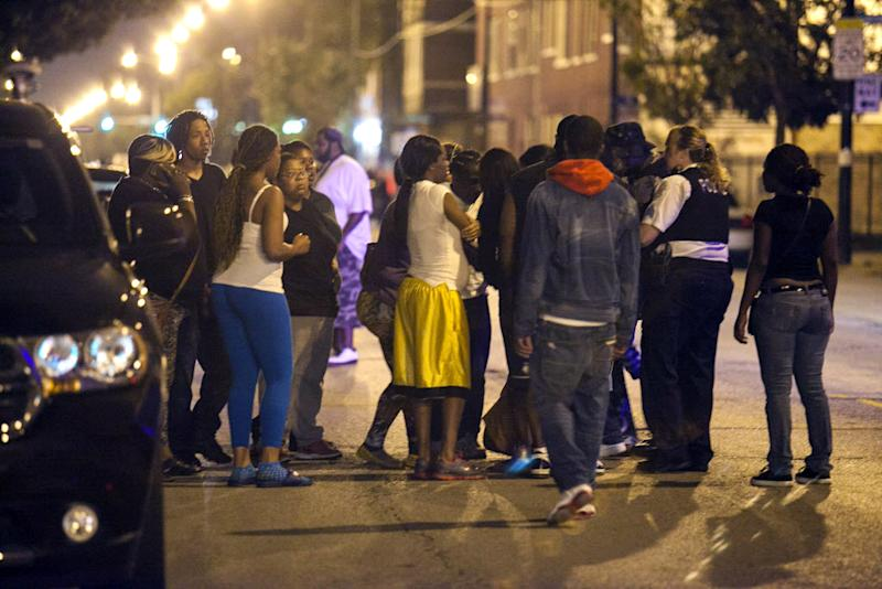 In this Thursday, Sept. 19, 2013, photo, bystanders convene near the scene of a shooting at Cornell Square Park in Chicago's Back of the Yard neighborhood that left multiple victims including a 3-year-old boy. Thursday night's attack was the latest violence in a city that has struggled to stop such shootings by increasing police patrols. (AP Photo/Sun-Times Media, Chandler West)