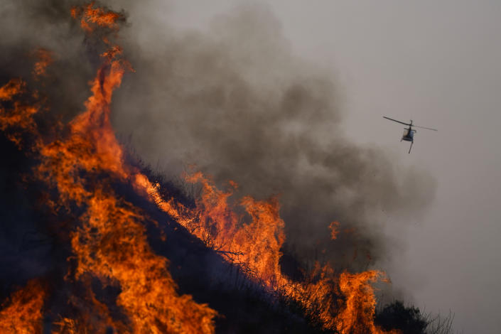 A helicopter flies away after dropping water over the Blue Ridge Fire burning along the 71 state highway Tuesday, Oct. 27, 2020, in Chino Hills, Calif. Crews tried to beat back two out-of-control wildfires in Southern California on Tuesday that have kept tens of thousands of people out of their homes even as another round of dangerous fire weather raises the risk for flames erupting across the state. (AP Photo/Jae C. Hong)