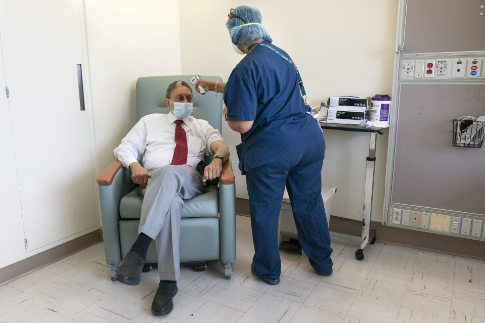 In this Wednesday, Feb. 10, 2021, photo Wallace Charles Smith, 72, who is a pastor at Shiloh Baptist Church, has his temperature taken before receiving his first COVID-19 vaccination by nurse Michelle Martin at United Medical Center in southeast Washington. (AP Photo/Jacquelyn Martin)