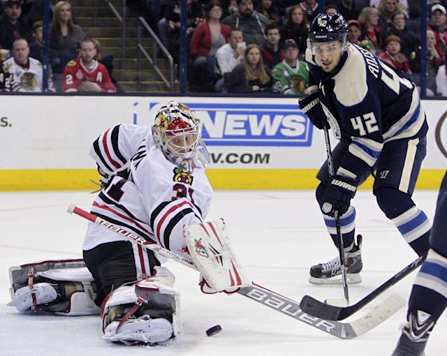 Chicago Blackhawks' Antti Raanta, left, of Finland, makes a save as Columbus Blue Jackets' Artem Anisimov, of Russia, waits for a rebound during the second period of an NHL hockey game on Friday, April 4, 2014, in Columbus, Ohio. (AP Photo/Jay LaPrete)