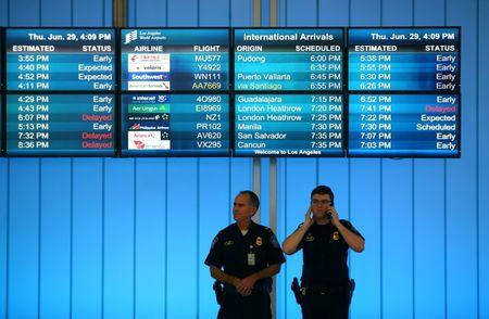 U.S. Customs and Immigration officers keep watch at the arrivals level at Los Angeles International Airport in Los Angeles, California