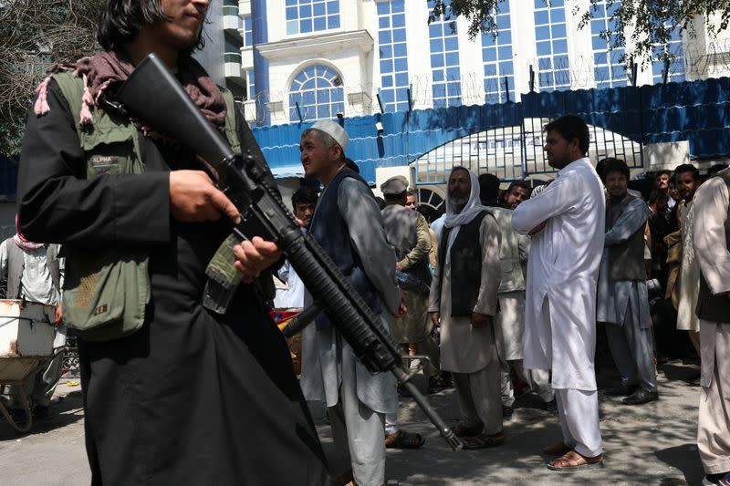 A Taliban security member holding a rifle ensures order in front of Azizi Bank in Kabul