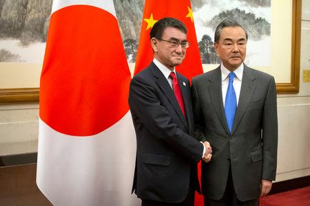 Japanese Foreign Minister Taro Kono shakes hands with Chinese Foreign Minister Wang Yi as he arrives for a meeting at the Diaoyutai State Guesthouse in Beijing,
