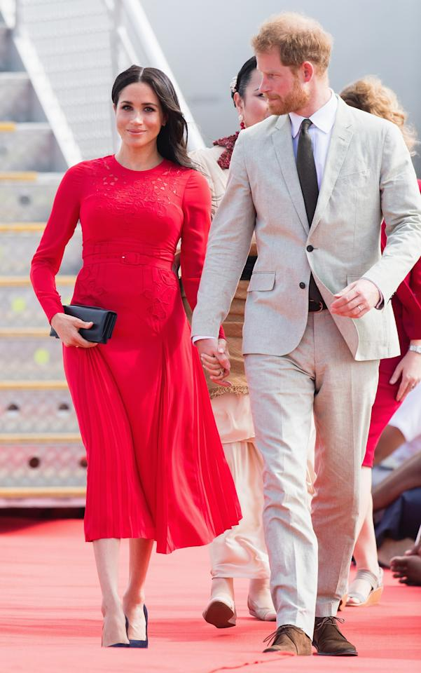 "The Duchess's dress was a nod to her host country, the red fabric meant to resemble the color of Tonga's flag. Markle previously wore Self-Portrait to the Queen's <a rel=""nofollow"" href=""https://www.glamour.com/story/meghan-markle-wears-self-portrait-for-queen-christmas-luncheon?mbid=synd_yahoo_rss"">Christmas luncheon</a> in 2017 and to an Invictus Games <a rel=""nofollow"" href=""https://www.glamour.com/story/meghan-markle-spring-dress-invictus?mbid=synd_yahoo_rss"">reception</a> in April 2018."