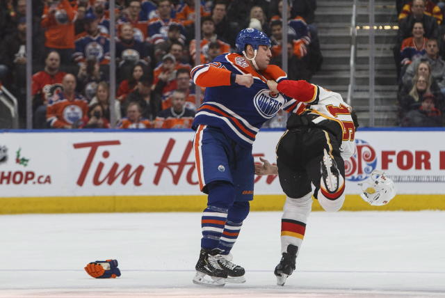 Calgary Flames' Anthony Peluso (16) and Edmonton Oilers' Milan Lucic (27) fight during first period NHL hockey action in Edmonton, Alberta on Sunday, Dec. 9, 2018. (Jason Franson/The Canadian Press via AP)