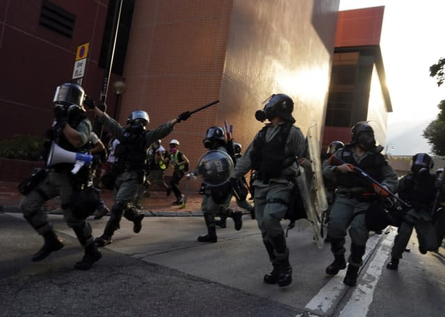 Police run during a confrontation with protesters