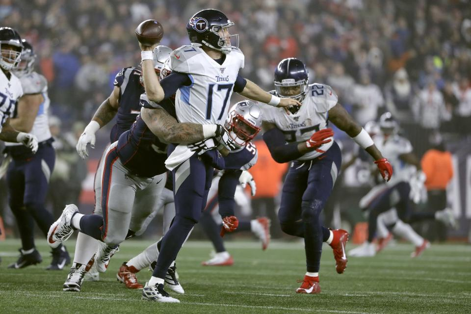 Tennessee Titans quarterback Ryan Tannehill passes while in the grasp of New England Patriots defensive tackle Lawrence Guy in the second half of an NFL wild-card playoff football game, Saturday, Jan. 4, 2020, in Foxborough, Mass. (AP Photo/Steven Senne)