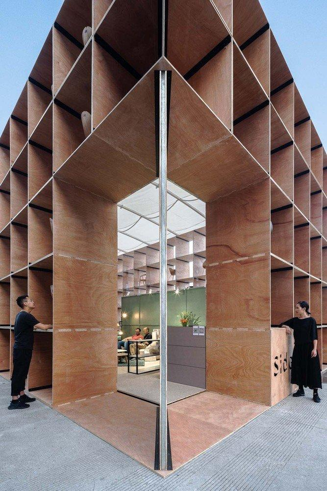 Large corner openings in the pavilion's perforated plywood facade give passerby a good look at the stylish furnishings within.