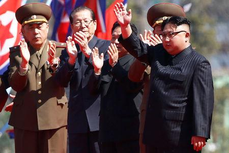 North Korean leader Kim Jong Un waves to people cheering during an opening ceremony of a newly constructed residential complex in Ryomyong street in Pyongyang
