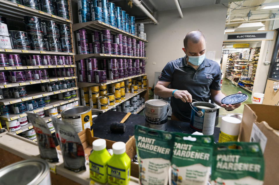Billy Wommack, purchasing director at the W.S. Jenks & Sons hardware, opens a gallon of paint at the mixing station of the hardware store's paint department, Friday, Sept. 24, 2021, in northeast Washington. The chemical shortages, and a near doubling of oil prices in the past year, mean higher prices for many goods. (AP Photo/Manuel Balce Ceneta)