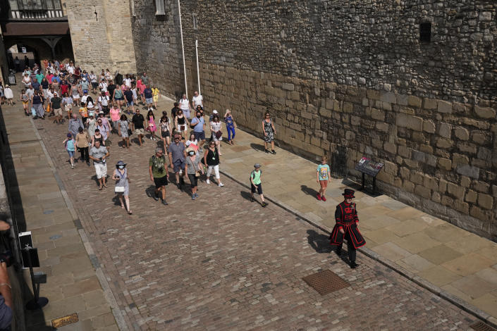"""On what some have called """"Freedom Day"""", marking the end of coronavirus restrictions in England, visitors follow as Yeoman Warder Barney Chandler leads the first tour of the Tower of London in 16 months since the start of the coronavirus outbreak, in London, Monday, July 19, 2021. Beginning Monday, face masks will no longer be legally required and with social distancing rules shelved, but mask rules will remain for passengers on the London transport network.(AP Photo/Matt Dunham)"""
