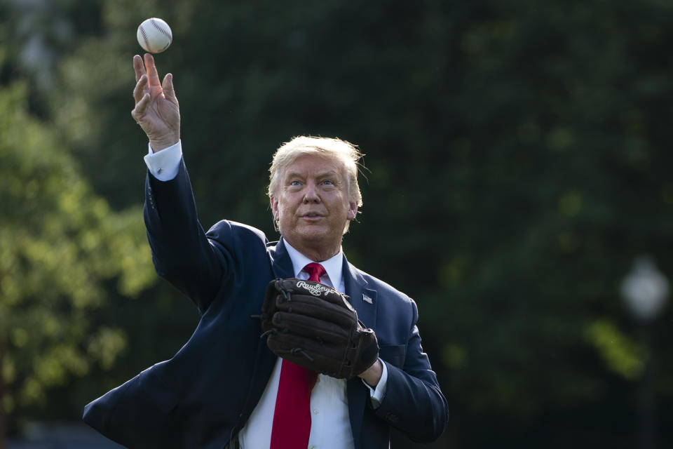 Donald Trump, in a suit and with a baseball glove, throws a baseball.