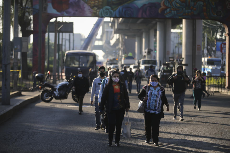 Commuters, looking for an alternate form of transportation, walk near a collapsed elevated section of the subway, in Mexico City, Tuesday, May 4, 2021. The elevated section of the metro collapsed and sent rail cars plunging toward a busy boulevard late Monday, killing at least 23 people and injuring at least 79, city officials said. (AP Photo/Fernando Llano)