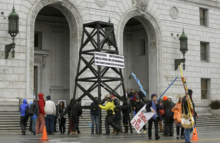 FILE - In this Feb. 6, 2015, file photo, protesters prepare to take down a makeshift oil derrick that was set up in front of the California State Office Building to protest fracking in San Francisco. On Friday, April 23, 2021, California Gov. Gavin Newsom announced he would halt all new fracking permits in the state by January 2024. He also ordered state regulators to plan for halting all oil extraction in the state by 2045. (AP Photo/Jeff Chiu, File)