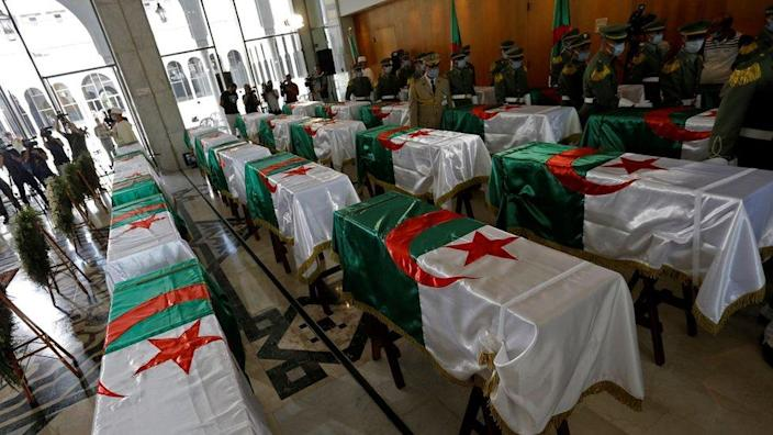 A soldier stands guard next to the national flag-draped coffins containing the remains of 24 Algerian resistance fighters decapitated during the French occupation, at the Moufdi-Zakaria culture palace in Algiers, Algeria, 04 July 2020.