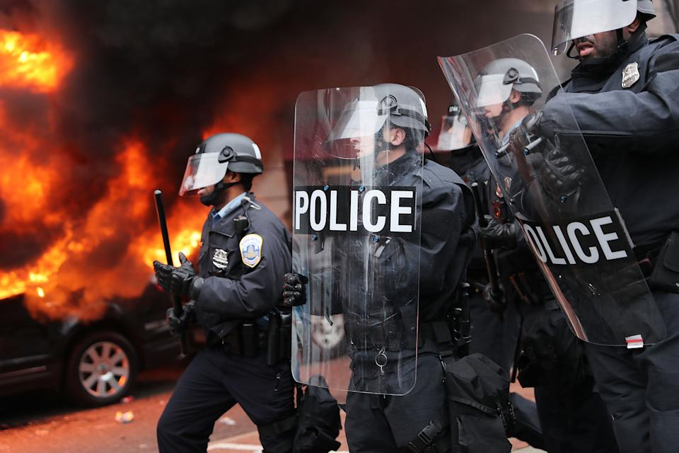 Police in riot gear move towards demonstrators in downtown Washington DC after a limousine was set on fire during Donald Trump's inauguration. (Getty Images)