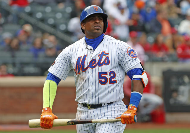 FILE - In this Sunday, April 1, 2018 file photo, New York Mets Yoenis Cespedes (52) holds his broken bat as he looks at a video replay of his flyout to deep left field during the third inning of a baseball game against the St. Louis Cardinals in New York. Mets outfielder Yoenis Cespedes had surgery to remove bone calcification in his left heel, the second of two foot operations New York hopes will enable him to return to action at some point next year. (AP Photo/Kathy Willens, File)