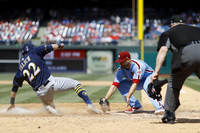 Philadelphia Phillies relief pitcher Adam Morgan, center, tags out Milwaukee Brewers' Christian Yelich, left, after Yelich tried to score on a passed ball during the sixth inning of a baseball game, Thursday, May 16, 2019, in Philadelphia. (AP Photo/Matt Slocum)