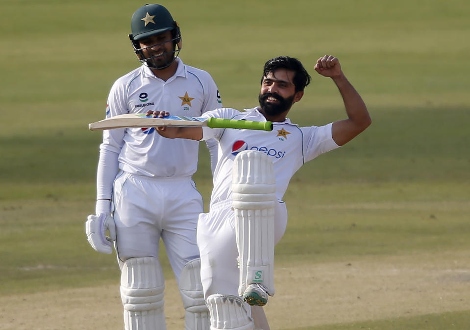 Pakistan's Fawad Alam, right, celebrates after scoring century while his teammate Faheem Ashraf watches during the second day of the first cricket test match between Pakistan and South Africa at the National Stadium, in Karachi, Pakistan, Wednesday, Jan. 27, 2021. (AP Photo/Anjum Naveed)
