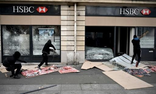 Demonstrators in Paris, some masked and hooded, broke shop windows along their route and threw projectiles at police in riot gear, who responded with tear gas