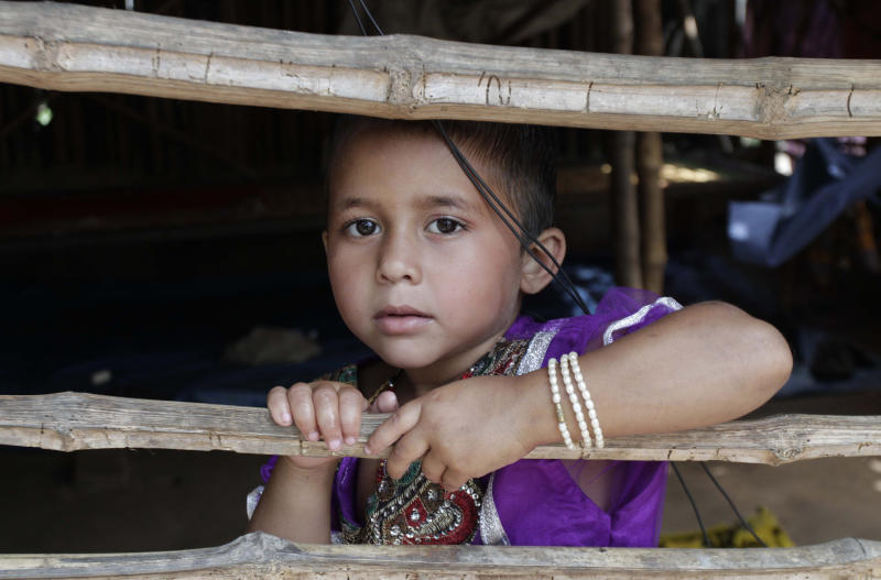 Rukshar Khatoon, the last person in India to contract polio, looks out from a bamboo fence at her home in Shahpara Village, 60 kilometers (40 miles) west of Kolkata, India, Thursday, March 27, 2014. In India, the scourge of polio ends with Khatoon, a lively 4-year-old girl who contracted the disease when she was a baby after her parents forgot to get her vaccinated. On Thursday, after three years with no new cases, the World Health Organization formally declared India polio-free. (AP Photo/Bikas Das)