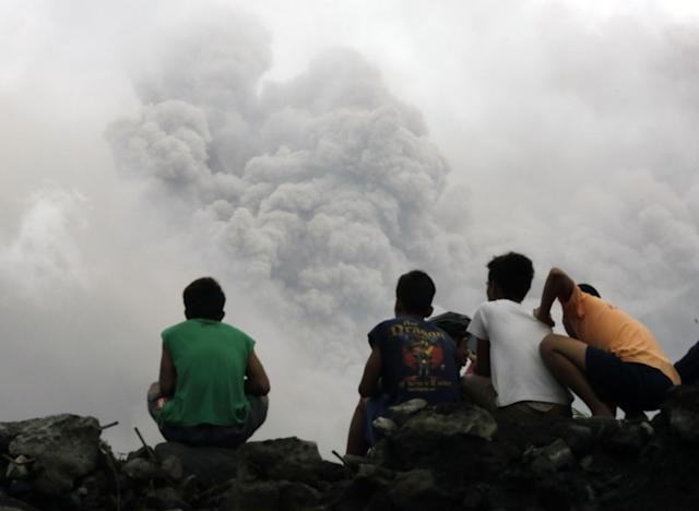 <p>Filipino villagers sit along the slopes of rumbling Mayon Volcano as it spews ash in Legaspi city, Albay province, Philippines, Jan. 16,2018. (Photo: Francis R. Malasig/EPA-EFE/REX/Shutterstock) </p>