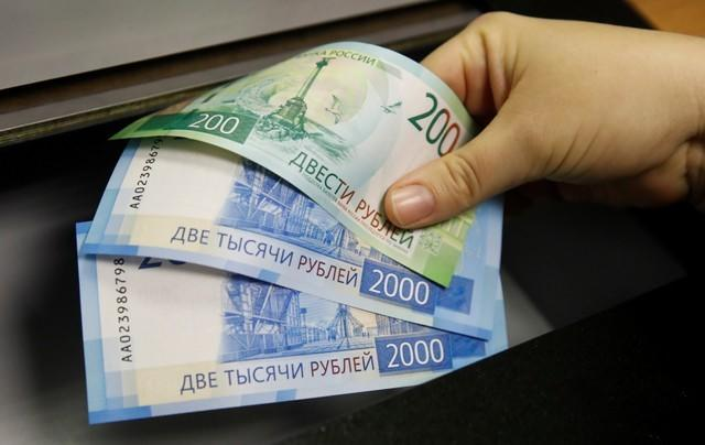 FILE PHOTO: A woman holds new 200 and 2,000 rouble banknotes in a bank in Moscow