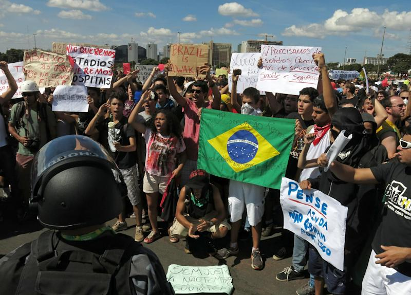 "Demonstrators protest in front of the National Stadium, some holding signs that read in Portuguese; ""We don't want stadiums, we want more hospitals,' and ""We don't need stadiums, we need education, health and security,"" before of the opening soccer match of the Confederations Cup between Brazil and Japan, in Brasilia, Brazil, Saturday, June 15, 2013. The protesters are complaining that too much money was spent for the World Cup while the local population continues to struggle. (AP Photo/Tales Azzoni)"