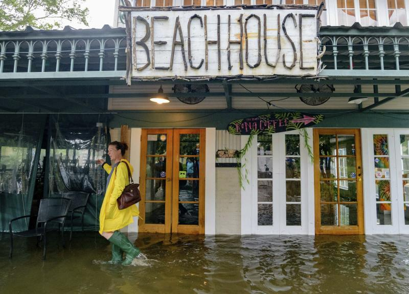 FILE - In this July 13, 2019, file photo Aimee Cutter, the owner of Beach House restaurant, walks through water surge from Lake Pontchartrain on Lakeshore Drive in Mandeville, La., ahead of Tropical Storm Barry. With earthquakes in California and Hurricane Barry striking states along the Gulf of Mexico and in the Midwest, small business owners should look at their insurance policies and determine how well covered they'd be in the event of a natural disaster. (AP Photo/Matthew Hinton, File)
