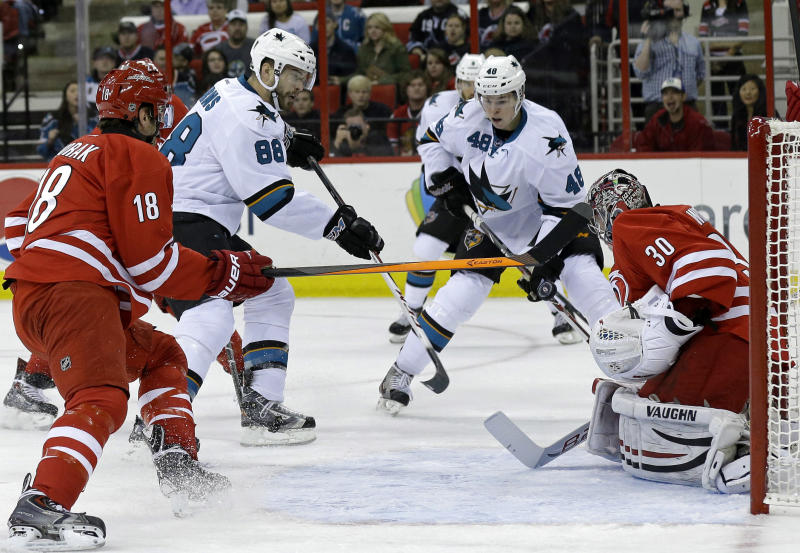 Carolina Hurricanes goalie Cam Ward (30) defends against San Jose Sharks' Brent Burns (88) as Sharks' Tomas Hertl (48), of the Czech Republic, and Hurricanes Radek Dvorak (18), of the Czech Republic, look on during the first period of an NHL hockey game in Raleigh, N.C., Friday, Dec. 6, 2013. (AP Photo/Gerry Broome)
