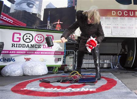 """Jody Watkins smashes old computers as part of """"Good Riddance Day"""" in Times Square in New York, December 28, 2013. REUTERS/Carlo Allegri"""