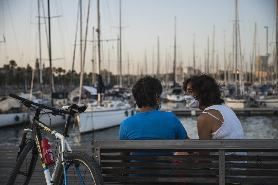 BARCELONA, SPAIN - JULY 27: People, wearing protective face masks, sit on a bench at Port Vell on July 27, 2020 in Barcelona, Spain. Spanish officials insisted it was still safe to travel to the country despite a recent rise in coronavirus (COVID-19) cases, which led the UK government to reimpose a 14-day quarantine on arrivals from Spain. The Catalonian government had recently issued a stay-at-home recommendation that included the regional capital, Barcelona. (Photo by Cesc Maymo/Getty Images)