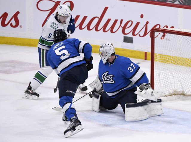 Winnipeg Jets goaltender Connor Hellebuyck (37) makes a save on Vancouver Canucks' Brock Boeser (6) as Luca Sbisa (5) defends during the third period of an NHL hockey game Tuesday, Jan. 14, 2020, in Winnipeg, Manitoba. (Fred Greenslade/The Canadian Press via AP)