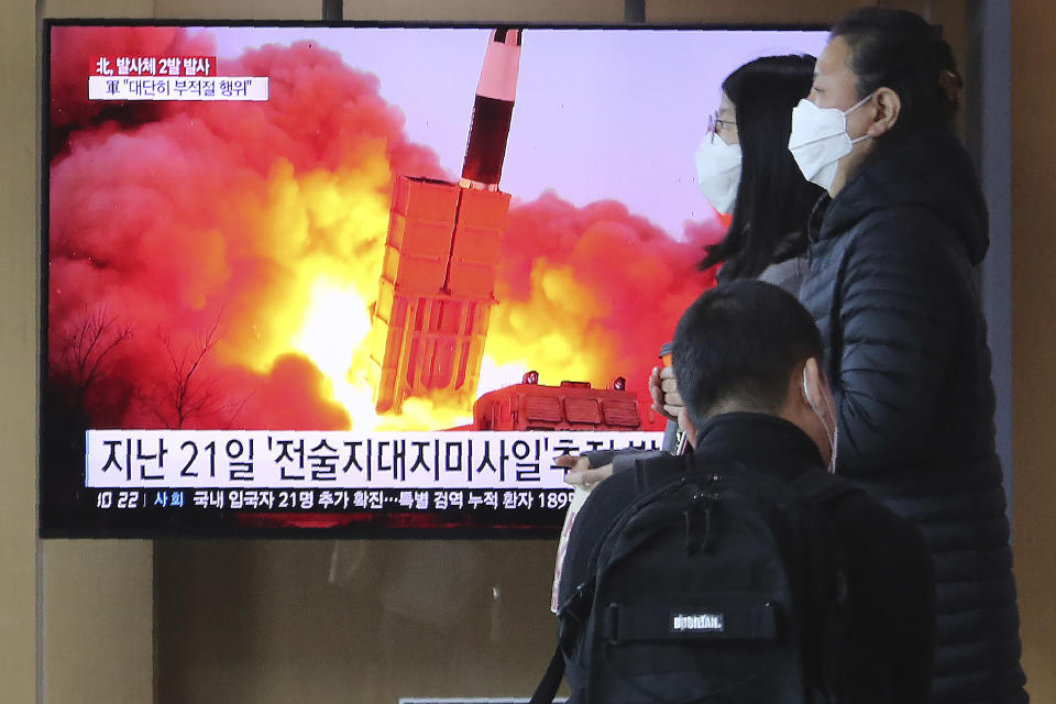 """People pass by a TV screen showing a file image of North Korea's missile launch during a news program at the Seoul Railway Station in Seoul, South Korea, Sunday, March 29, 2020. North Korea on Sunday fired two suspected ballistic missiles into the sea, South Korea said, calling it """"very inappropriate"""" at a time when the world is battling the coronavirus pandemic. The Korean letters read: """"March 21, Tactical Missile."""" (AP Photo/Ahn Young-joon)"""