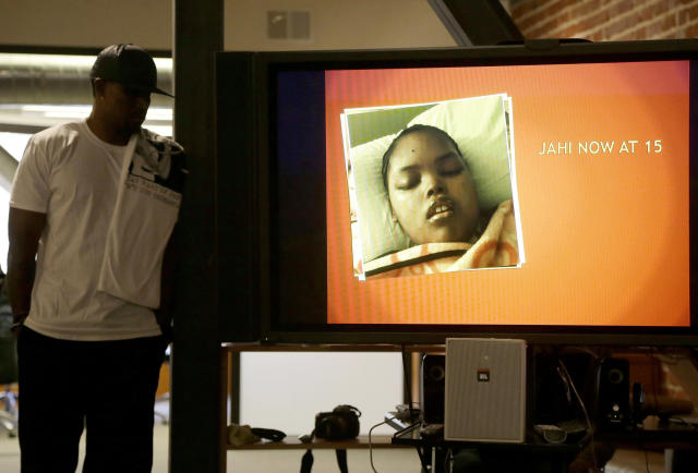 In this Dec. 23, 2015, photo, Jahi McMath is shown on a video screen next to her uncle Timothy Whisenton, at a news conference in San Francisco. (AP Photo/Jeff Chiu, file)