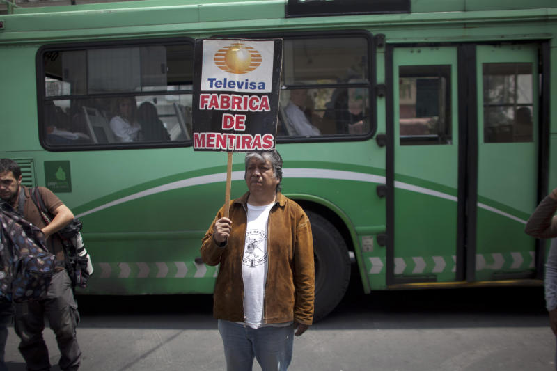 """A man protests against major Mexican TV network Televisa in front of the Democratic Revolution Party (PRD) headquarters where Andres Manuel Lopez Obrador, presidential candidate, gave a news conference, in Mexico City, Friday, July 06, 2012. Televisa and other major networks are accused by some of biased coverage of the presidential campaign in favor of Enrique Pena Nieto, candidate of the Institutional Revolutionary Party (PRI). The banner reads in Spanish: """"Televisa, fabric of lies"""". (AP Photo/Alexandre Meneghini)"""