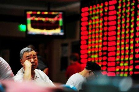 An investor sits in front of an electronic board showing stock information at a brokerage house in Nanjing, Jiangsu province, China, September 27, 2016. REUTERS/Stringer