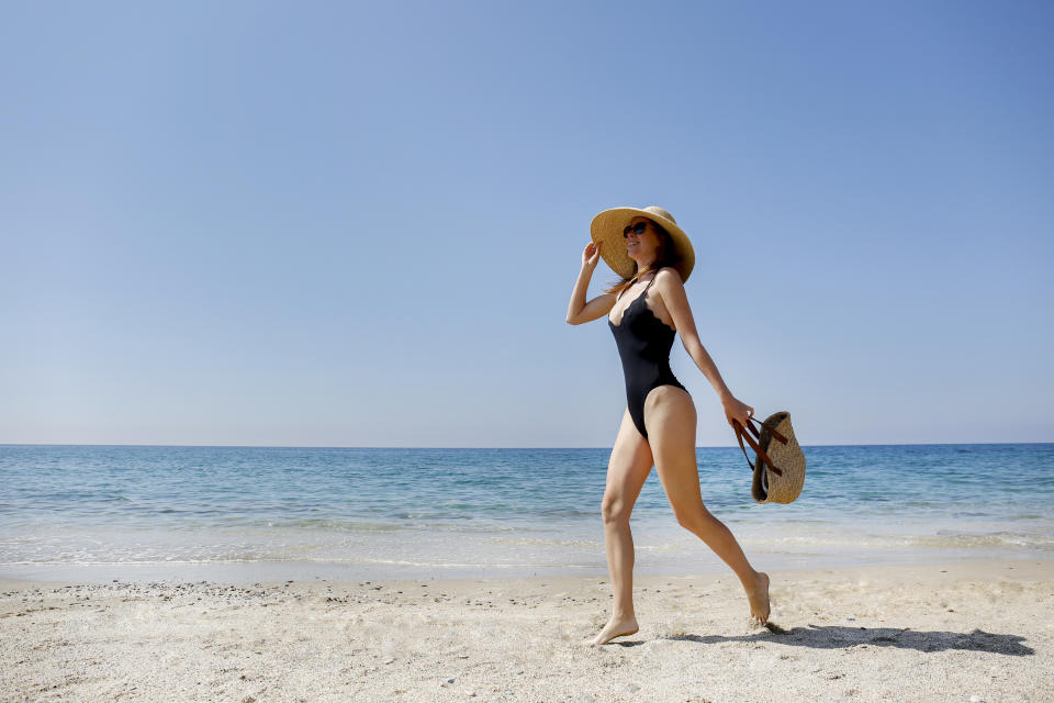 Young beautiful woman wearing one piece swimsuit, broad brim straw hat posing with a beach bag. Female fashion model at sandy beach on beautiful sunny day. Mediterranean sea background. Copy space