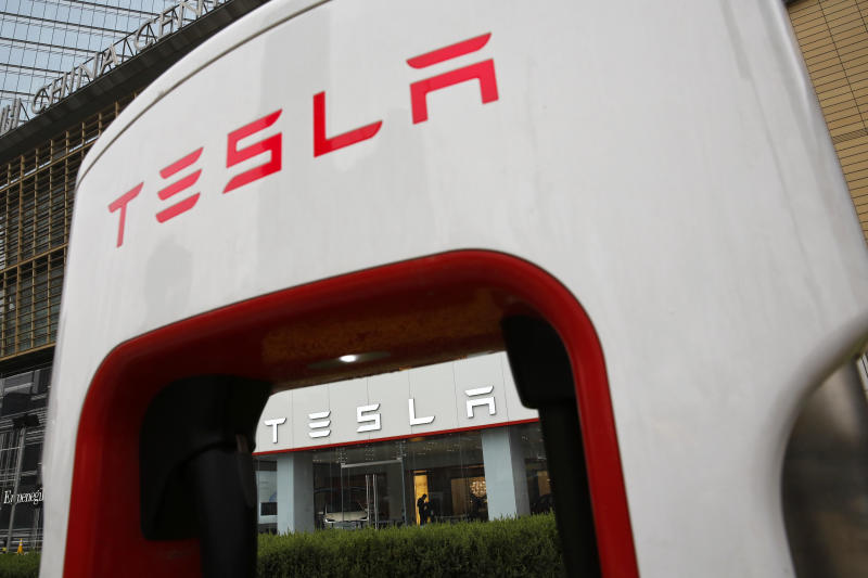 FILE - In this April 5, 2018, file photo, a sales person stands inside a Tesla electric vehicle showroom in Beijing. Electric car producer Tesla will build its first factory outside the United States in Shanghai under an agreement signed Tuesday, July 10, 2018, becoming the first wholly foreign-owned automaker in China. (AP Photo/Andy Wong, File)