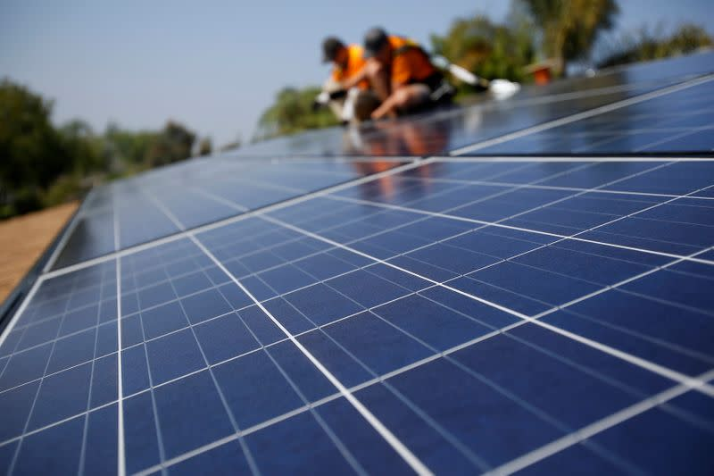 FILE PHOTO: Vivint Solar technicians install solar panels on the roof of a house in Mission Viejo