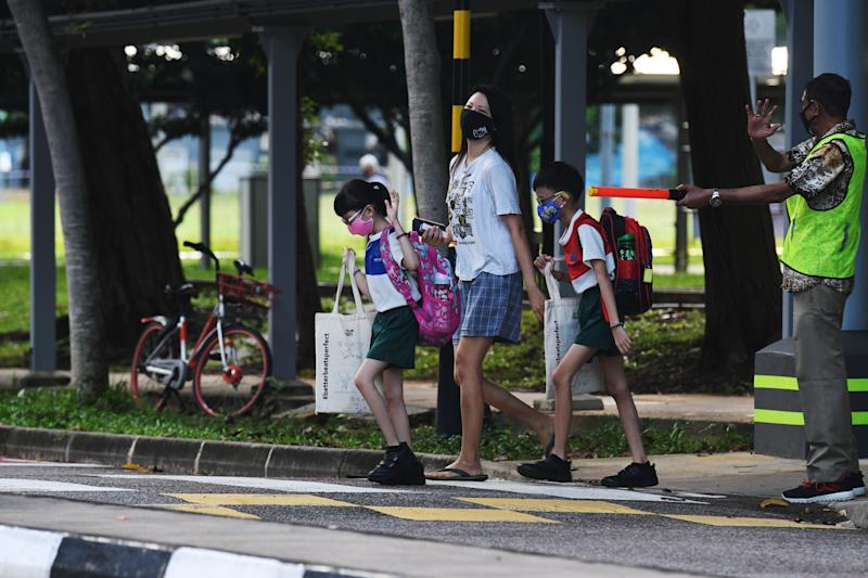 "SINGAPORE, June 2, 2020 -- Primary school students wearing face masks are seen on their way to school in Singapore on June 2, 2020. Schools in Singapore reopened on Tuesday as the state embarked on a phased reopening from a COVID-19 ""circuit breaker"" period to curb the spread of the coronavirus. (Photo by Then Chih Wey/Xinhua via Getty) (Xinhua/xinjiapo via Getty Images)"