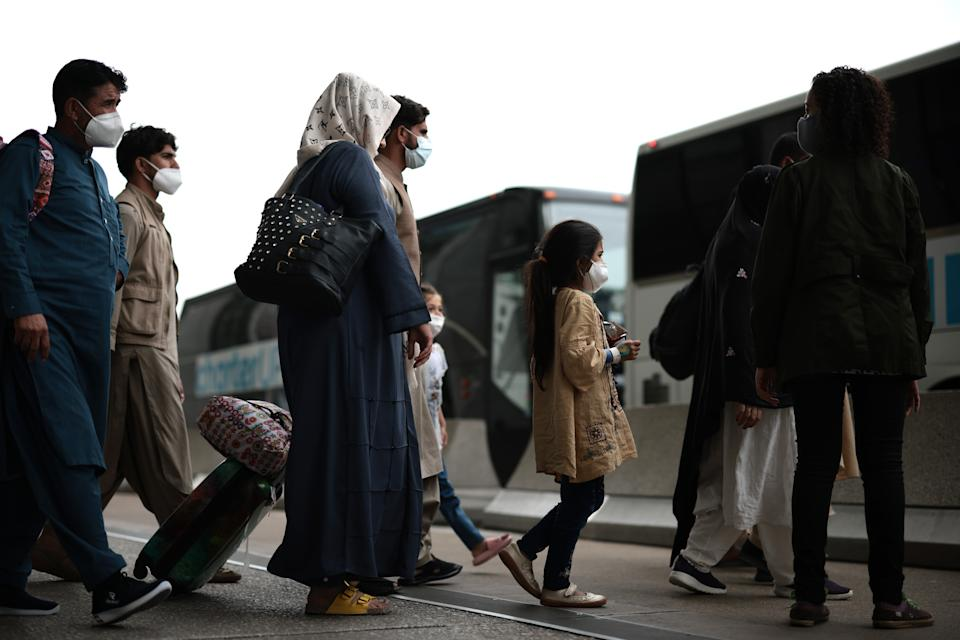 Refugees walk to board a bus at Dulles International Airport after being evacuated from Kabul following the Taliban takeover of Afghanistan on August 31, 2021 in Dulles, Virginia. (Anna Moneymaker/Getty Images)