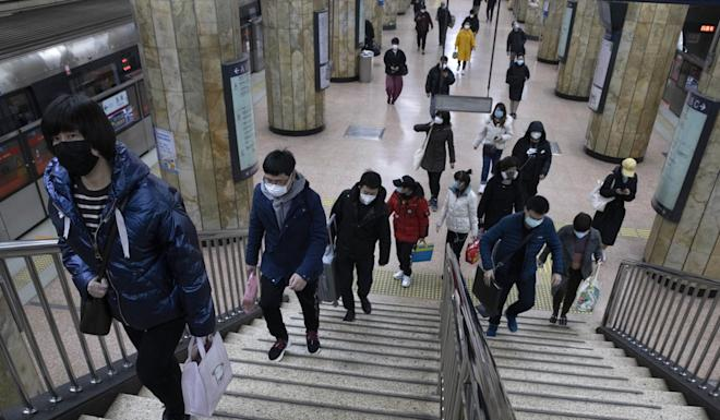 Passengers walk up the stairs during morning peak at a subway station in Beijing Monday, March 9, 2020. With almost no new Covid-19 cases being reported in Beijing, workers are slowly returning to their offices with masks on and disinfectant in hand. Photo: AP