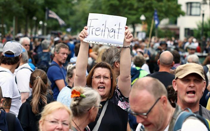 A protester holds a sign reading 'Freedom' at a protest against Covid-19 restrictions in Berlin, Germany on 1 August 2021 - Christian Mang/Reuters