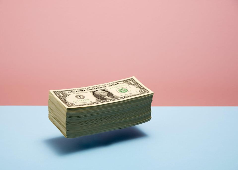 An image of a stack of money floating on a colorful background.
