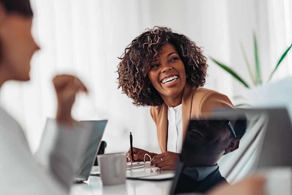 Portrait of cheerful african american businesswoman discussing and smiling at the meeting with colleagues